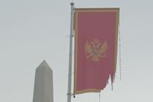 <p>Поцијепана застава крај споменика</p>